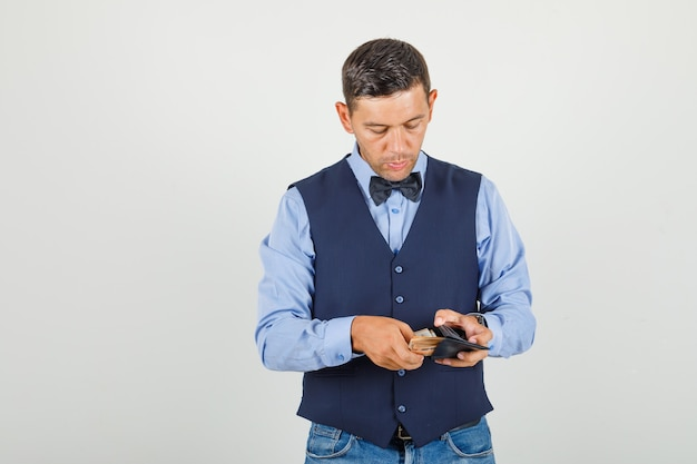 Jeune homme prenant de l'argent du portefeuille en costume
