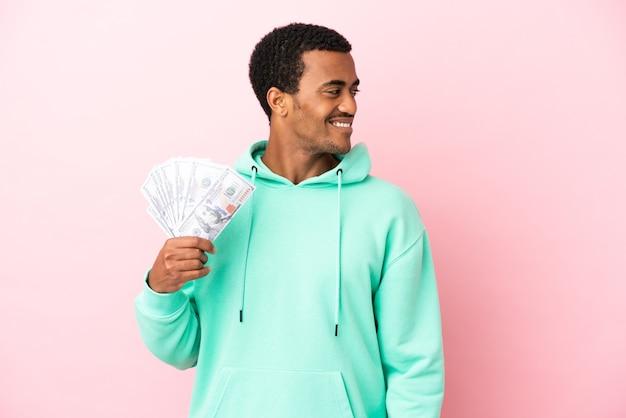 Jeune homme prenant beaucoup d'argent sur fond rose isolé regardant sur le côté et souriant