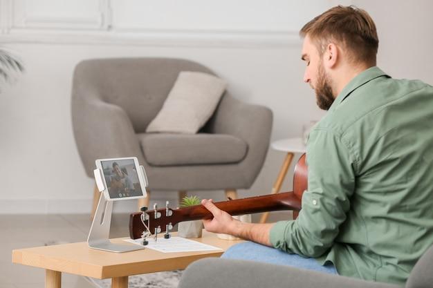 Jeune homme prenant des cours de musique en ligne à la maison