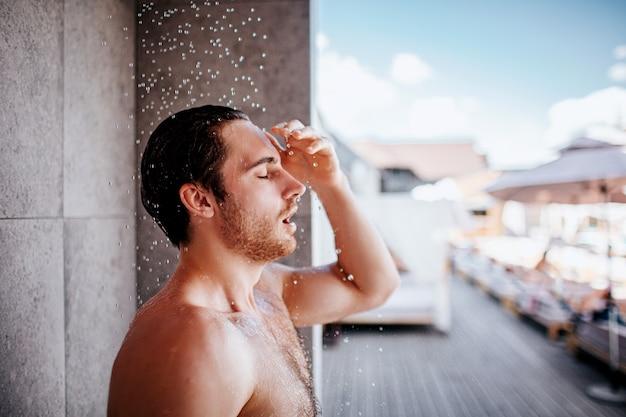 Jeune homme prenant une douche à l'extérieur.
