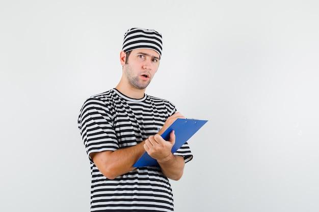 Jeune homme prenant des notes sur le presse-papiers en t-shirt, chapeau et à la vue de face, hésitant.