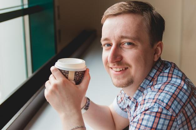 Jeune homme prenant une pause café au café