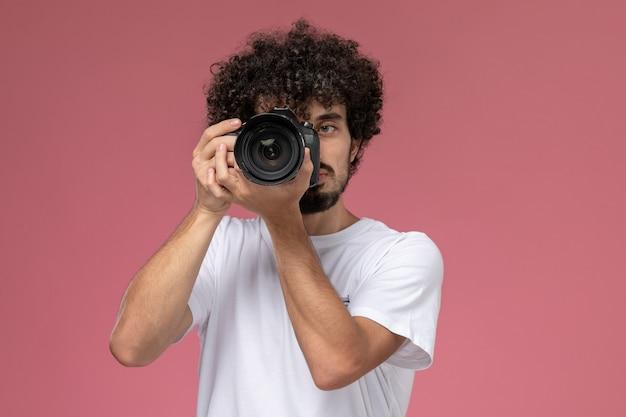 Jeune homme prenant une photo au sérieux