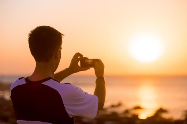 Jeune homme prenant photo du coucher de soleil sur la mer
