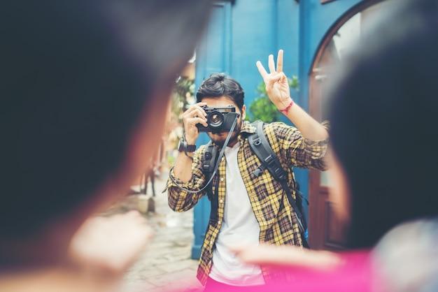 Jeune homme prenant selfie de ses amis lors d'un voyage en ville ensemble.