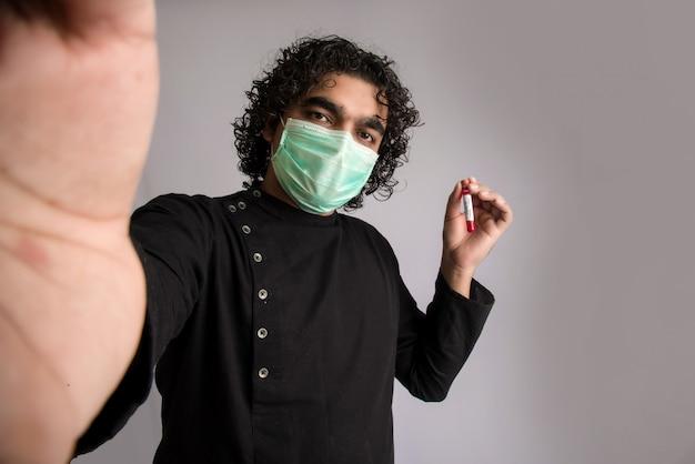 Jeune homme prenant un selfie avec un tube à essai avec un échantillon de sang pour le coronavirus ou l'analyse 2019-ncov.