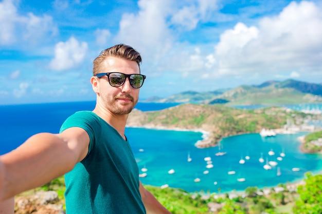 Jeune homme prenant selfie avec vue sur le port anglais depuis shirley heights, antigua, paradis bay sur une île tropicale dans la mer des caraïbes