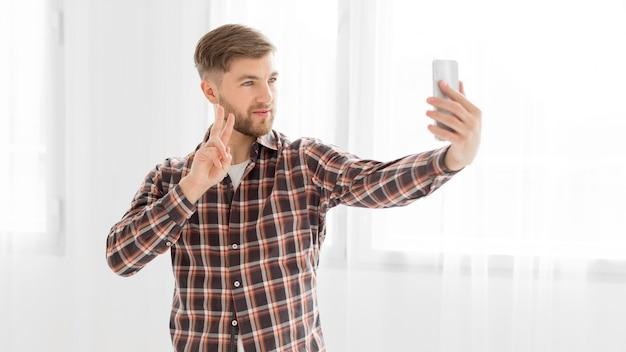 Jeune homme prenant selfie