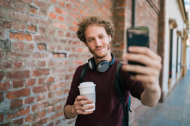 Jeune homme prenant des selfies avec téléphone.
