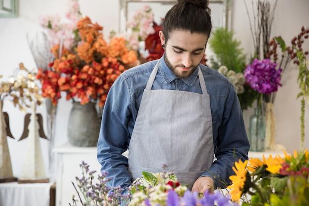 Jeune homme prenant soin de son bouquet de fleurs dans le magasin de fleurs
