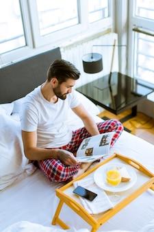 Jeune homme prenant son petit déjeuner au lit et lisant un magazine dans la chambre