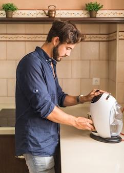 Jeune homme, prendre café, de, espresso capsule, machine à café