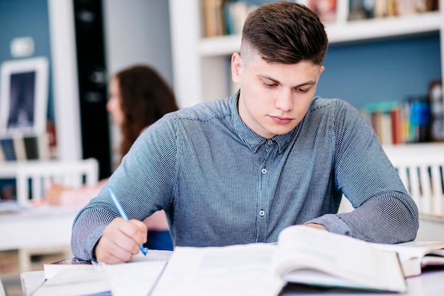 Jeune homme, prendre des notes dans la bibliothèque