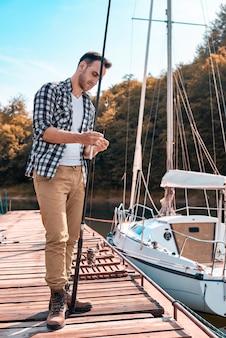 Jeune homme préparant sa canne à pêche