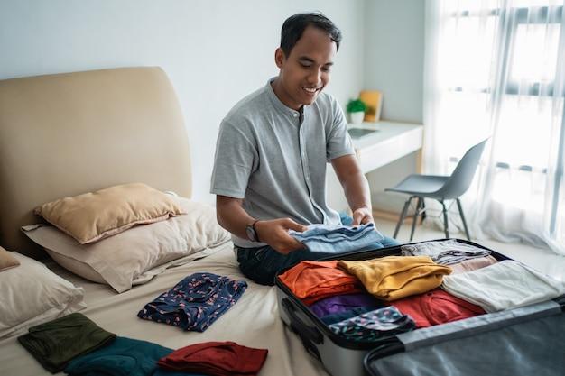 Jeune homme préparant ses vêtements mis dans la valise