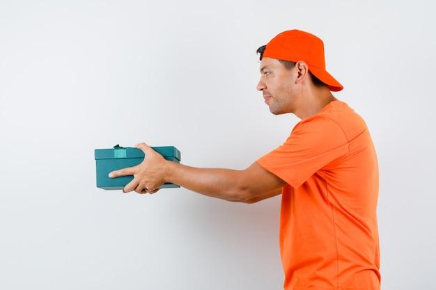 Jeune homme présentant une boîte-cadeau en t-shirt et casquette orange et à la recherche amicale.