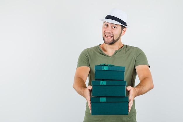Jeune homme présentant des coffrets cadeaux en t-shirt vert et chapeau et à la joyeuse