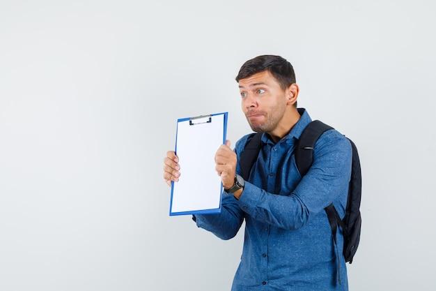 Jeune homme présentant le presse-papiers en chemise bleue et ayant l'air effrayé. vue de face.
