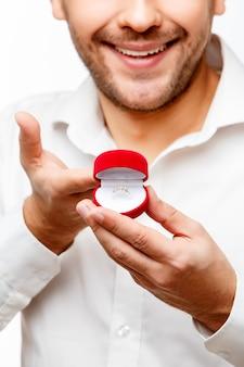 Jeune homme présentant quelque chose dans une petite boîte