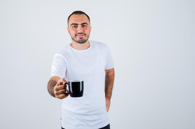 Jeune homme présentant une tasse de thé en t-shirt blanc et pantalon noir et l'air heureux