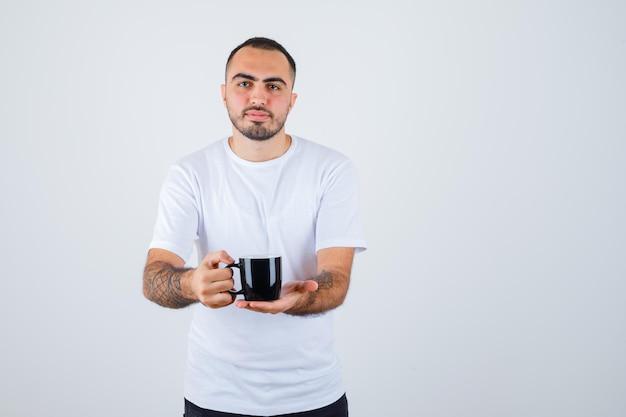 Jeune homme présentant une tasse de thé en t-shirt blanc et pantalon noir et à la grave