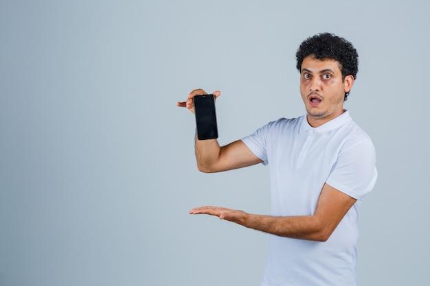 Jeune homme présentant un téléphone portable en t-shirt blanc et l'air étonné, vue de face.