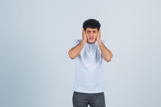 Jeune homme pressant les mains sur les oreilles en t-shirt blanc et jeans et à l'air harcelé , vue de face.
