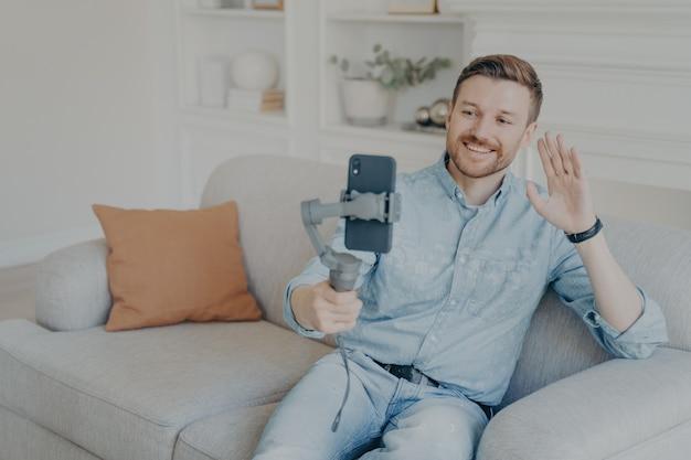 Jeune homme profitant d'une conversation vidéo avec des amis, regardant l'écran du téléphone et agitant la main, homme barbu joyeux tenant un smartphone avec un stabilisateur de cardan à main alors qu'il était assis sur un canapé dans le salon