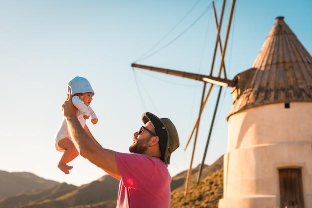 Un jeune homme profitant avec son fils dans le parc naturel de cabo de gata, un moulin de la ville de san jose, almeria