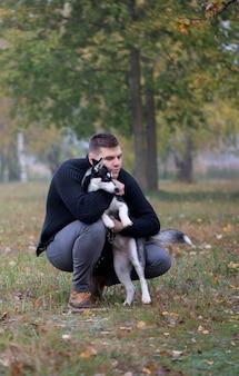 Jeune homme propriétaire d'animal avec chien dans le parc d'automne