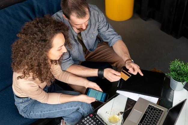 Jeune homme propriétaire de café avec barbe assis sur un canapé et pointant sur l'écran de la tablette tout en parlant au serveur de menu
