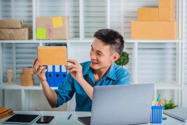 Jeune homme propriétaire d'entreprise pme tenant une boîte en carton.