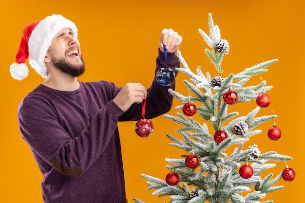 Jeune homme en pull violet et bonnet de noel jouets suspendus sur l'arbre de noël