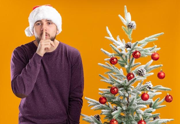 Jeune homme en pull violet et bonnet de noel regardant la caméra en faisant un geste de silence à côté de l'arbre de noël sur fond orange