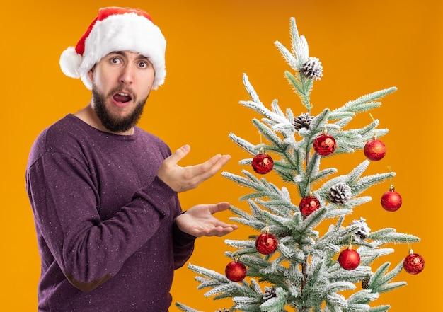 Jeune homme en pull violet et bonnet de noel à la surprise et surpris debout à côté de l'arbre de noël sur fond orange