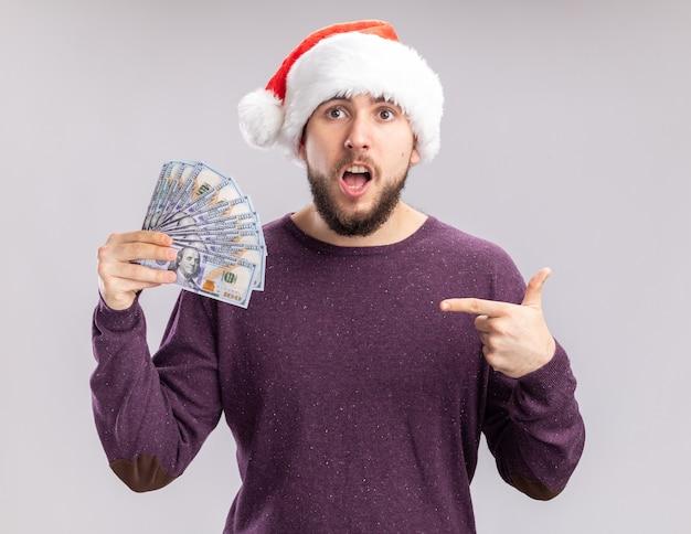 Jeune homme en pull violet et santa hat holding cash pointant avec l'index à l'argent à la surprise debout sur fond blanc