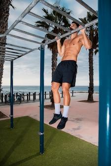 Jeune homme pulls exercice routine en plein air
