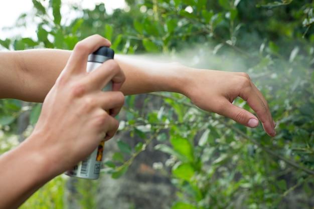 Jeune homme pulvérisant un anti-moustique