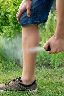 Jeune homme pulvérisant un insectifuge contre les moustiques dans la forêt