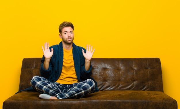Jeune homme en pyjama qui a l'air nerveux, inquiet et inquiet, en disant que ce n'est pas de ma faute ou que je ne l'ai pas fait