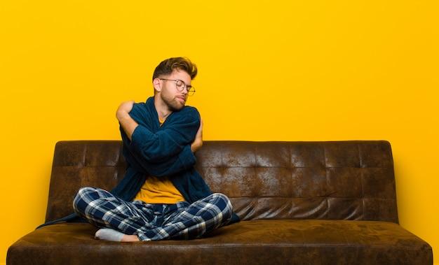 Jeune homme en pyjama se sentant amoureux, souriant, se câlinant et s'embrassant, restant célibataire, égoïste et égocentrique. assis sur un canapé