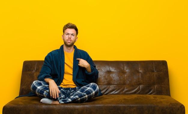 Un jeune homme en pyjama se sentant confus, perplexe et peu sûr de lui, se pointant pour se demander et demander qui, moi?