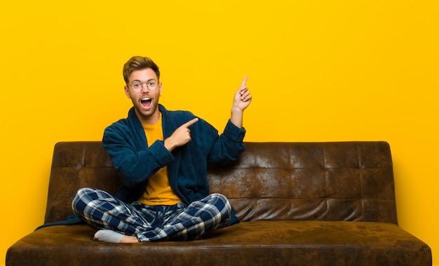 Jeune homme en pyjama se sentant joyeux et surpris, souriant avec une expression choquée et pointant vers le côté. assis sur un canapé