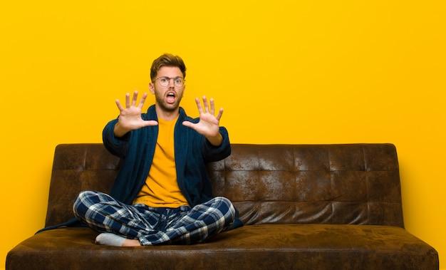 Jeune homme en pyjama se sentant terrifié, reculant et hurlant d'horreur et de panique, réagissant à un cauchemar