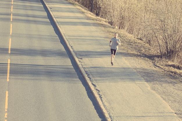 Jeune homme qui court dehors le long d'une route de montagne vide