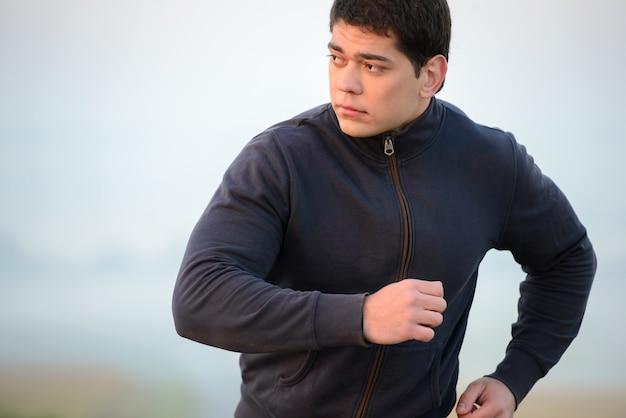 Jeune homme qui court à l'extérieur le matin.