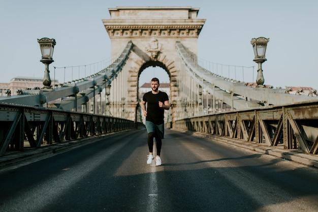 Jeune homme qui court sur le pont des chaînes à budapest, hongrie