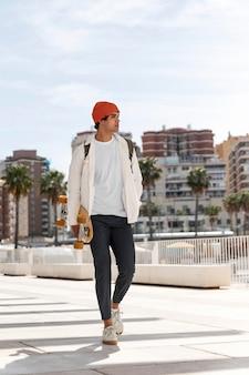 Jeune homme qui marche tout en tenant sa planche à roulettes