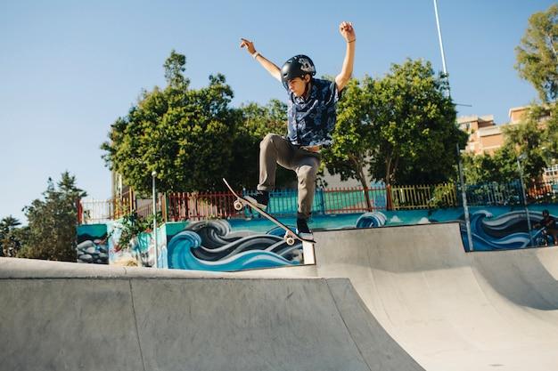 Jeune homme qui patine et saute