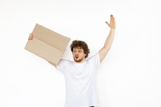 Jeune homme qui protestait avec un panneau vierge isolé sur fond de studio blanc
